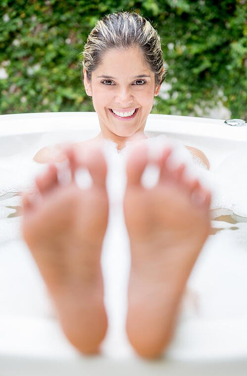 Beautiful woman taking a bubble bath and smiling