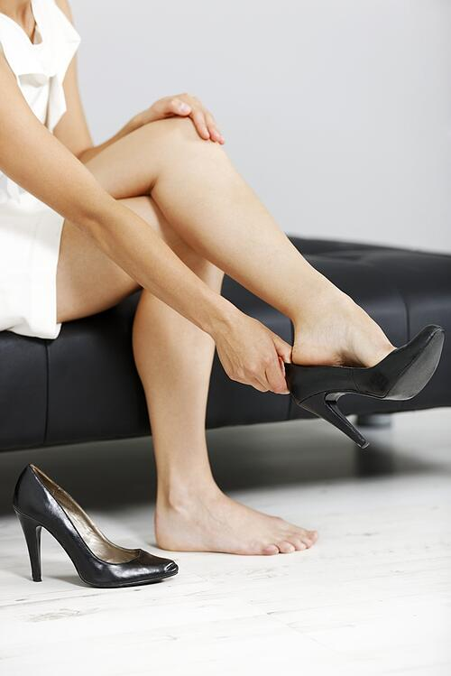 Beautiful young business woman taking her shoes off after a long day..jpeg