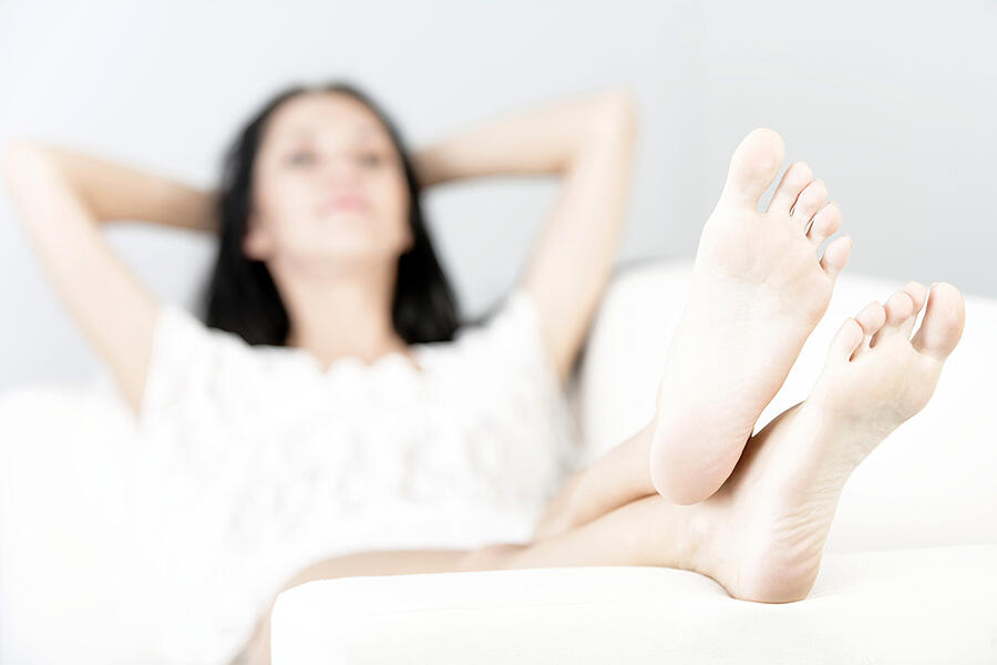 Beautiful young woman with long dark hair lying on her back on a white sofa at home with her feet up
