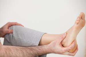 Chiropractor holding the heel of a patient in a room-1