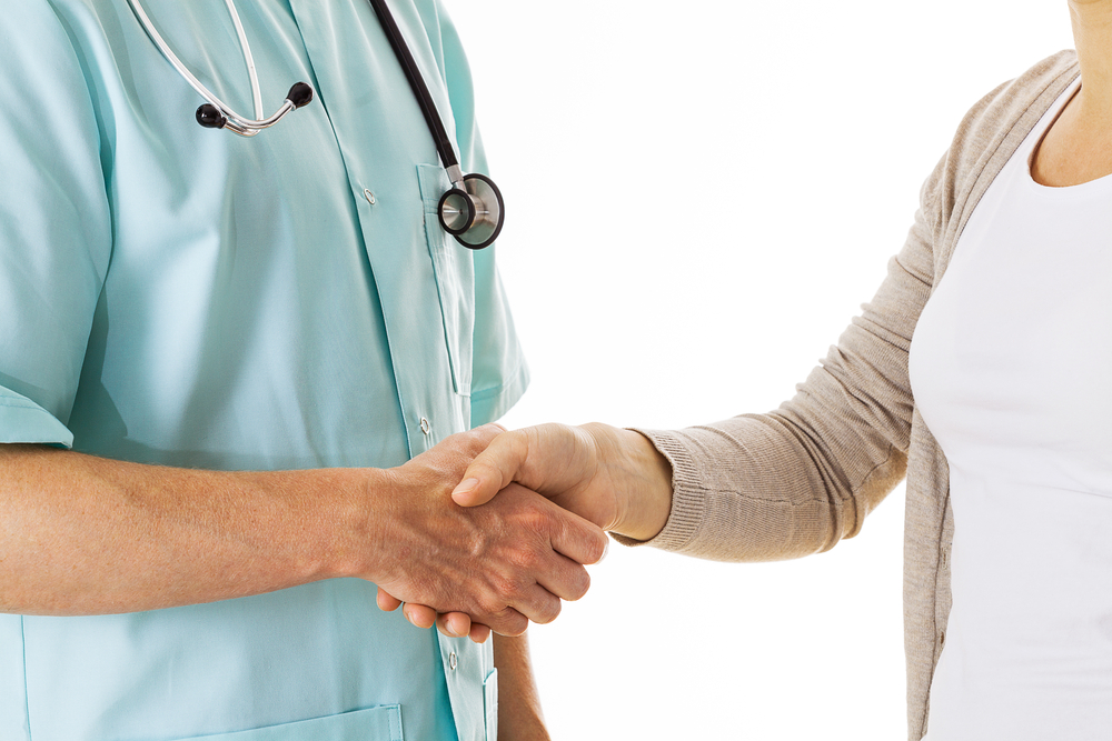 Doctor shaking hand with a patient, isolated background