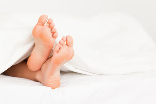 Feet in a bed against a white background
