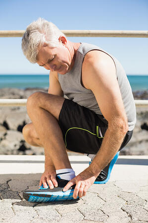Fit man gripping his injured ankle on a sunny day-1