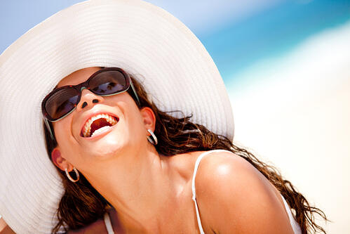 lady wearing sunglasses and sunhat on the beach
