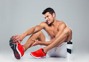 Portrait of a fitness man with foot pain over gray background-1