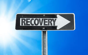 Recovery direction sign with a beautiful day