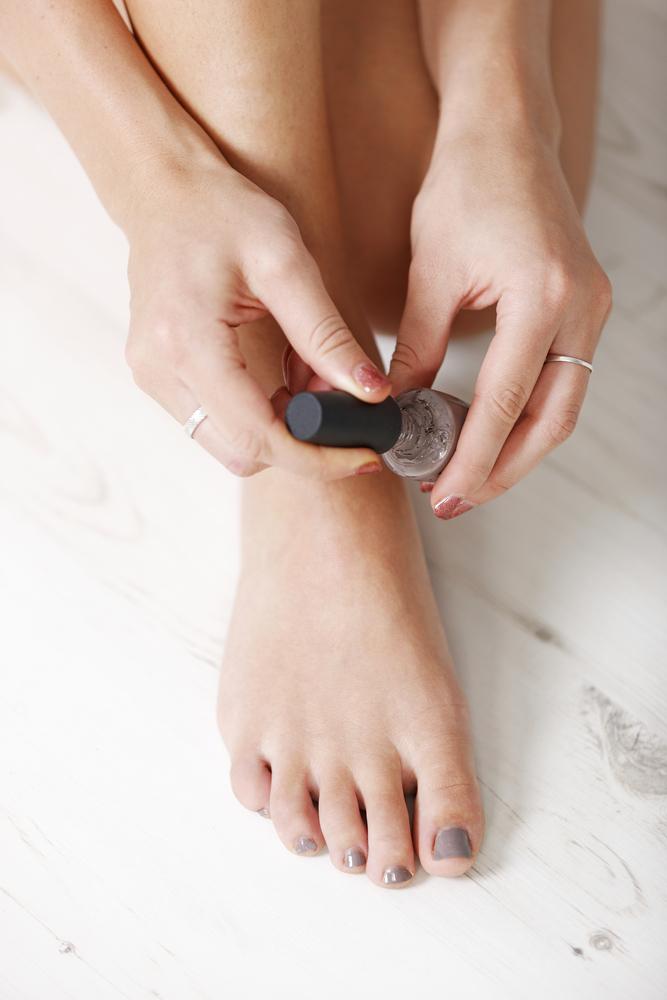 person painting toenails