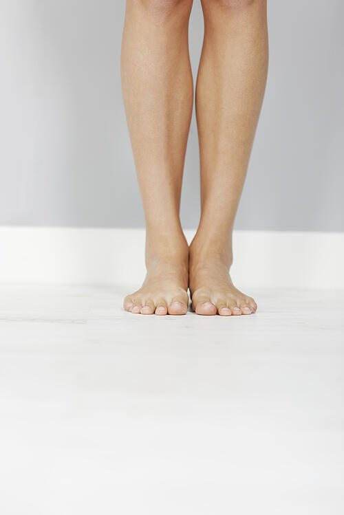 Young womans legs on wooden floor.