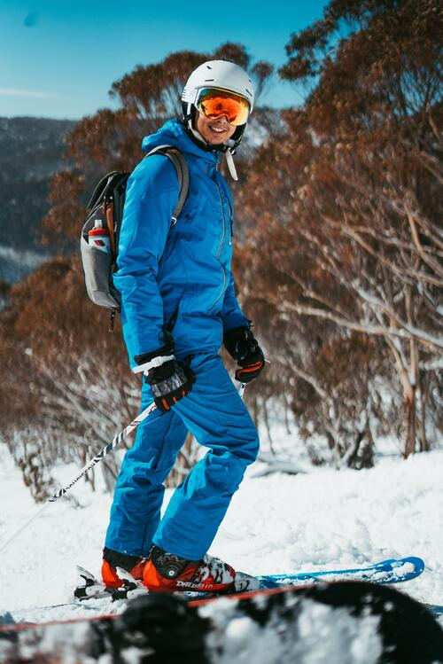 person walking in the snow with a blue snowsuit on