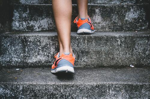 person wearing running shoes on stairs